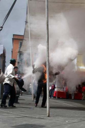 Socorristas rocian con extintores al dirigente indigena Ramiro Guillén Tapia, quen se prendió fuego