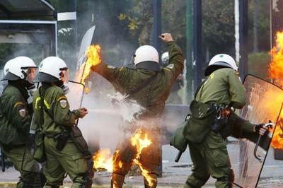 Un elemento de seguridad fue alcanzado por una de las bombas molotov lanzadas en las manifestaciones en Grecia contra el asesinato de un joven. Ap