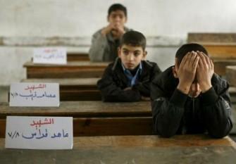 Jebaliya. Carteles con un nombre sustituyen en los mesabancos escolares a tres niños palestinos, de casi 300 que fallecieron en los ataques israelies en Gaza. Hoy se reanudaron clases. Ap
