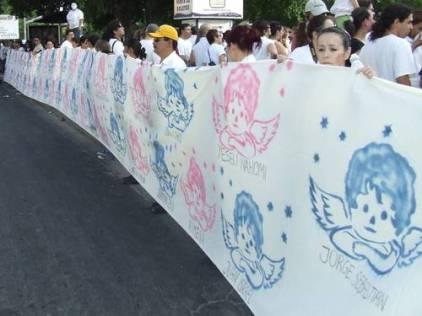 Una manta con 46 dibujos de ángeles con los nombres de los niños fallecidos fue desplegada durante la marcha en la capital sonorense. Foto Ulises Gutiérrez